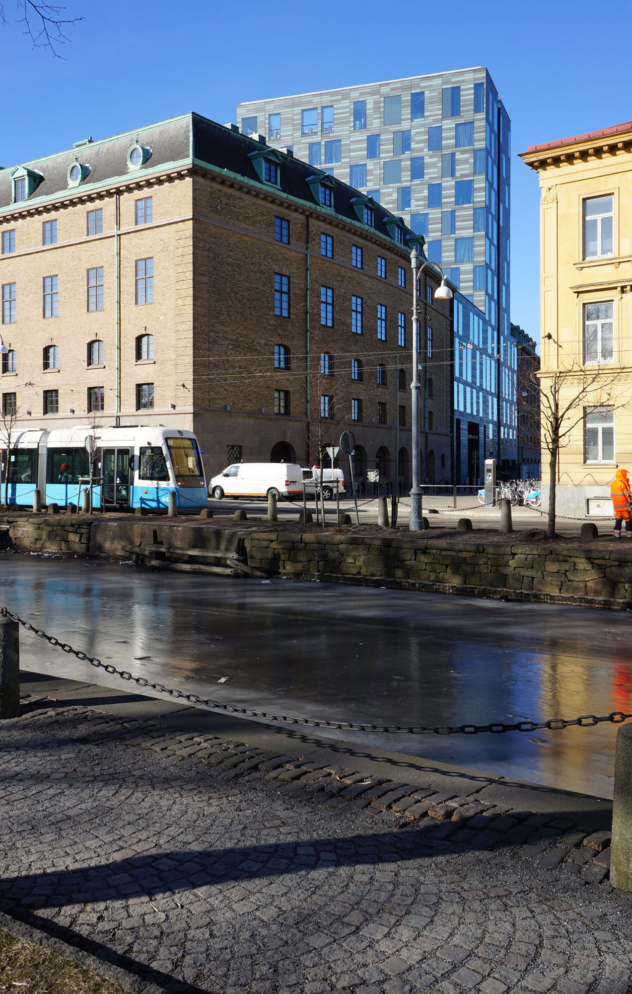 Streetside view of the Post Hotel located in Gothenburg, Sweden. The copper facade clad from Nordic Green Living copper is visible in the background. The sky is blue and it is daytime. There is ice inbetween the roads in front of the picture. A tram is visible.