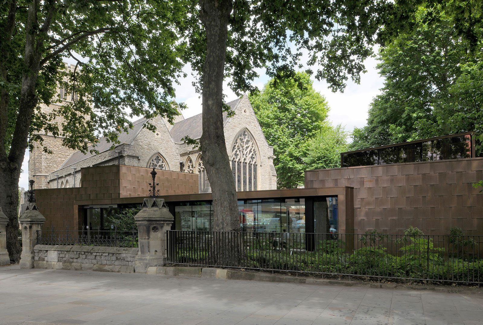 Street-view of the Garden Museum building which is clad in Nordic Bronze copper. Separating the building and the pedestrian walkway is traditional churchyard garden wall with iron bar fence. Behind all this is the church building.