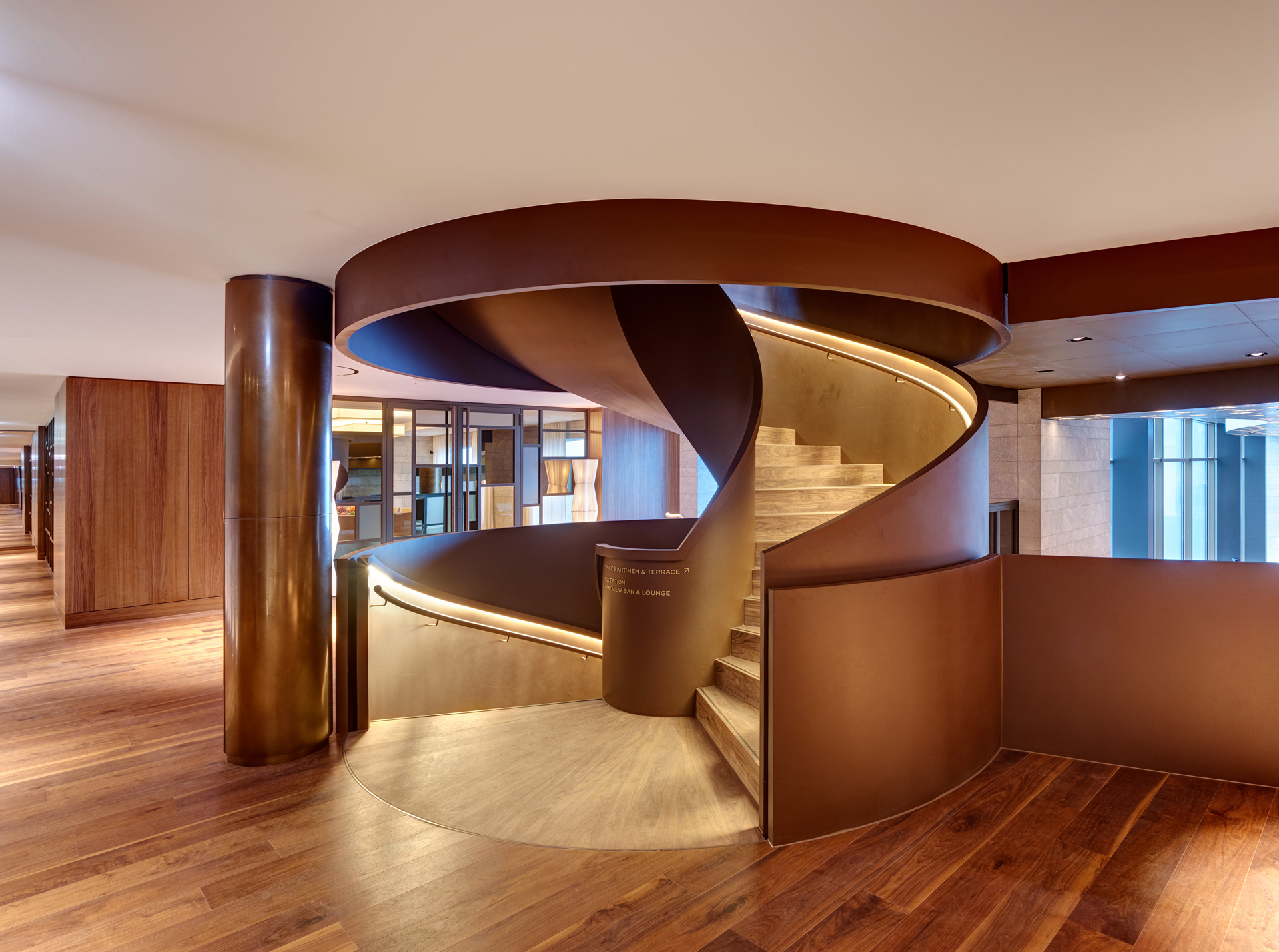 Circular staircase inside the Hotel Bürgenstock. Nordic Décor coated pillar is next to the staircase. The Staircase's outer parts are made from Nordic Décor and their surface is smooth matte-like. The Staircase steps and the floor have a wood finish.
