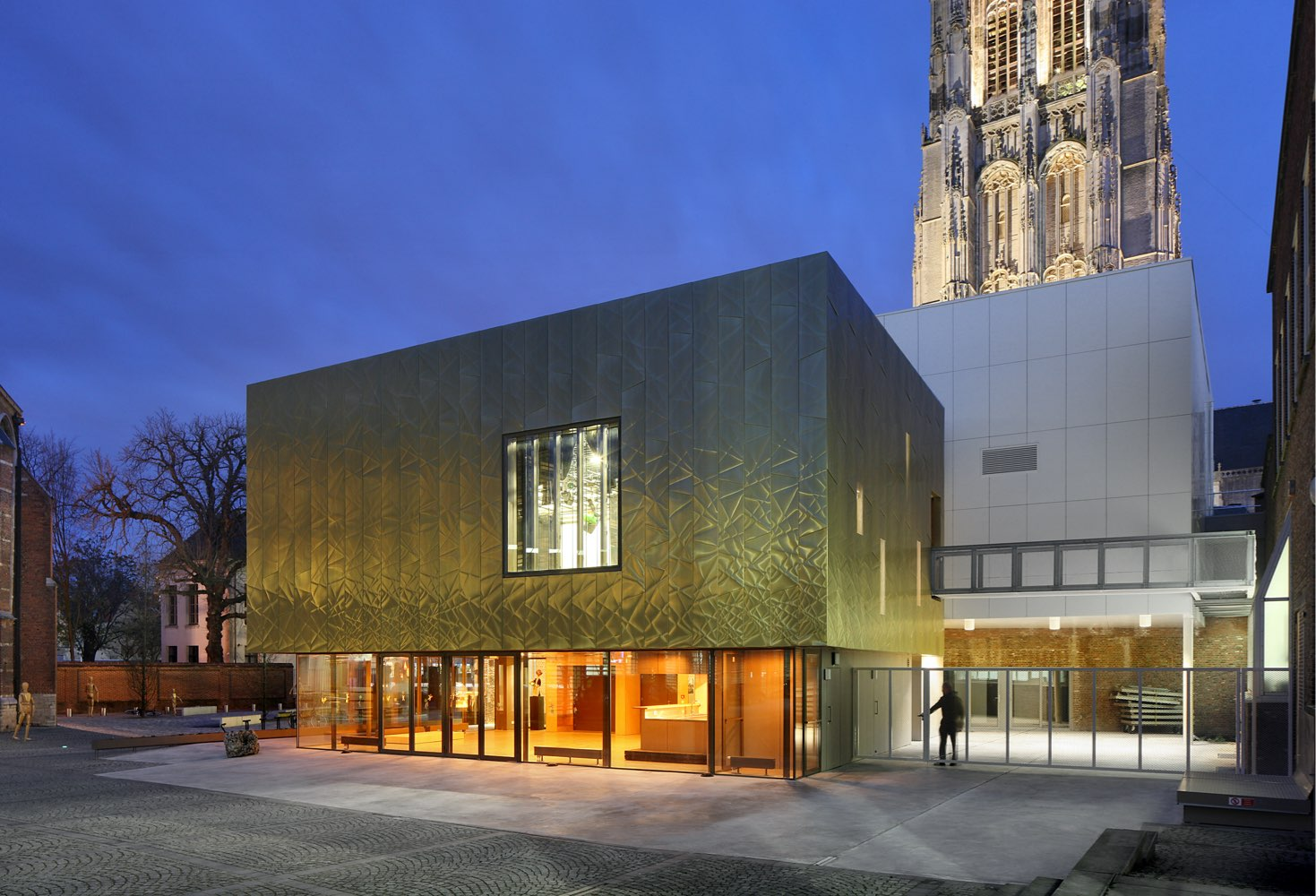 Outside view of The Moon Art Centre located in Mechelen, Belgium during nighttime. The building has light coming from the inside. The walls are clad from Nordic Royal Copper by Aurubis. A man is on the right o the building. An old, tall tower is in the background.