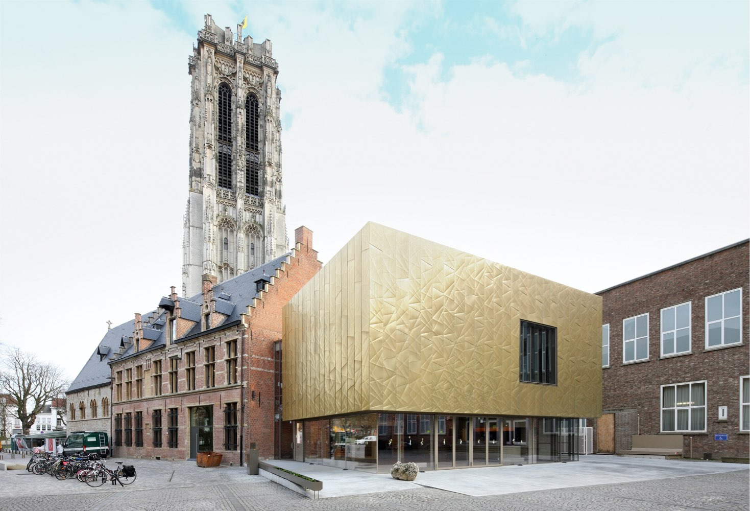 A view from the front of the Moon Art Centre located in Mechele, Belgium. The building has gold-coloured walls called Nordic Royal Copper, made by Aurubis. The facade has a singular window and multiple doorways. The copper walls have small folds and creases for aesthetics. It is daytime outside. Some bicycles can be seen in the photo. An old and tall tower is in the background.