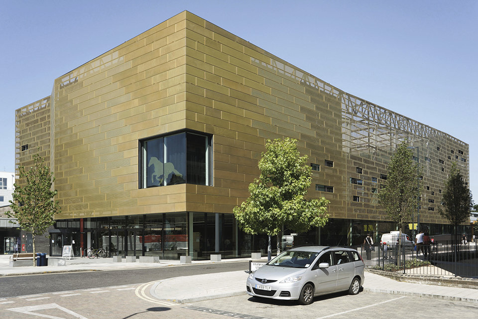 Front and Side facade of the Deptford Lounge located in London, UK. Walls are clad form Nordic Royal Copper by Aurubis and Nordic Copper. Copper is gold-coloured and reflects sunlight. The corner of the building has a large window on it. Front of the building has a tree, a road and a silver car.