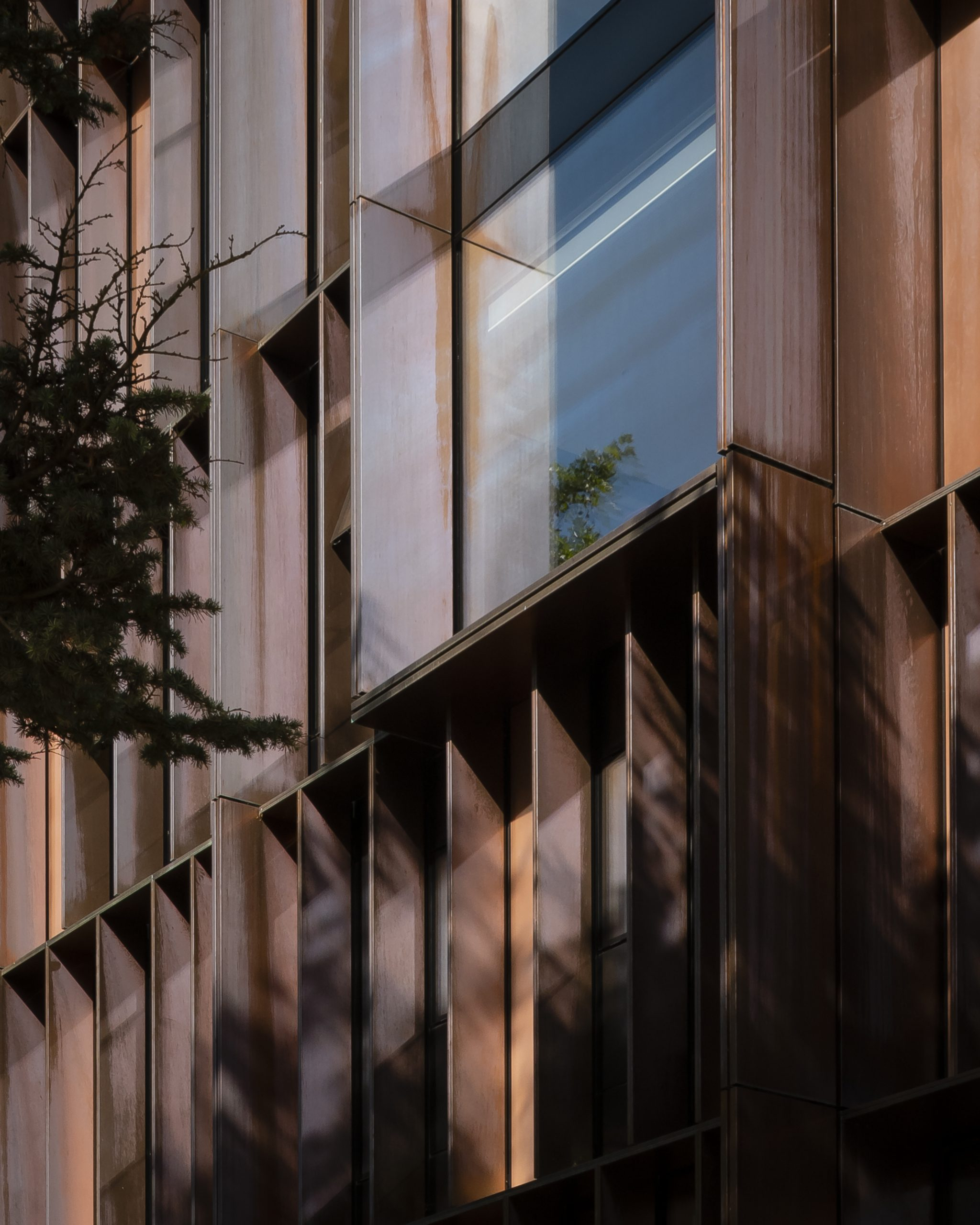A closeup of a copper-clad wall of Beecroft Building located in United Kingdom. The photo is cascading from right to left and some greenery is visible close by to the left. The copper walls are brown-coloured and are clad from copper produced by Nordic Copper and Aurubis.