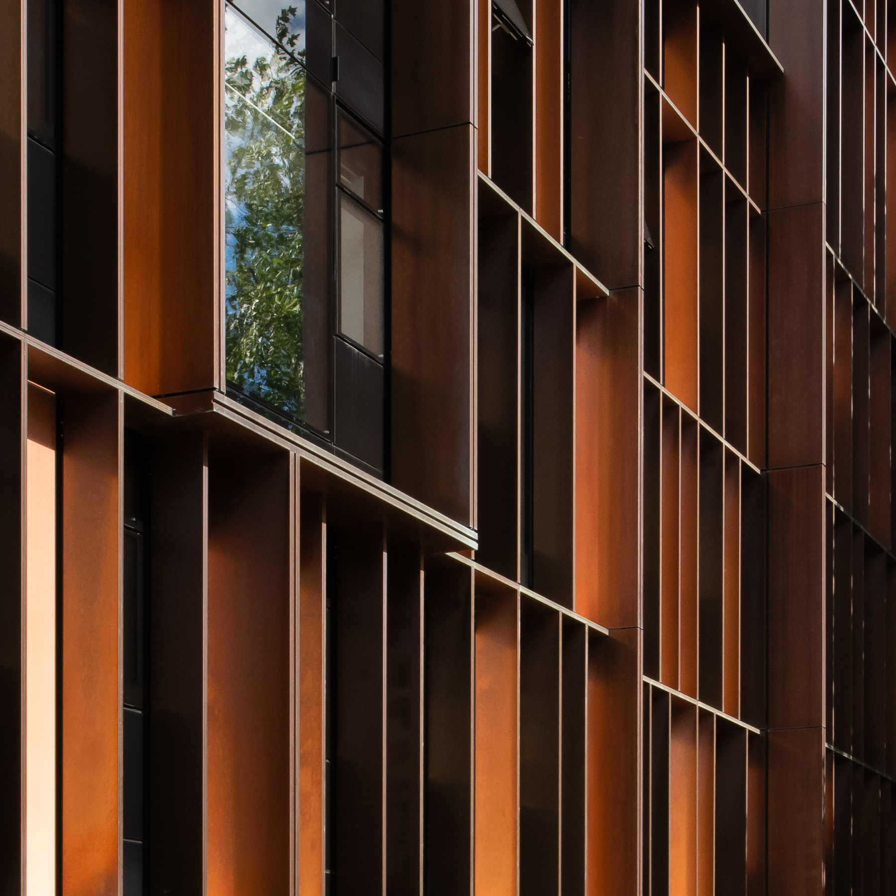 Close view of a copper wall of Beecroft Building located in United Kingdom. The wall is layered unorthodoxically. Walls are clad from brown-coloured copper by Aurubis and Nordic Copper. The photo has a singular rectangular window in the wall, surrounded by Nordic Brown Copper from Nordic Copper.
