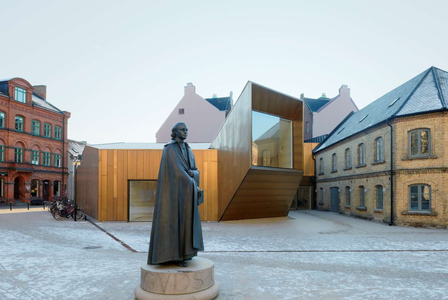 Domkyrkoforum located in Lund, Sweden. Front of the photo shows an erected dark grey statue. Behind the statue is a complex building clad from copper. The building is unorthodox. Building walls are clad form Nordic Copper by Aurubis. Background shows older cityscape buildings. It is daytime outside and the sky is grey.