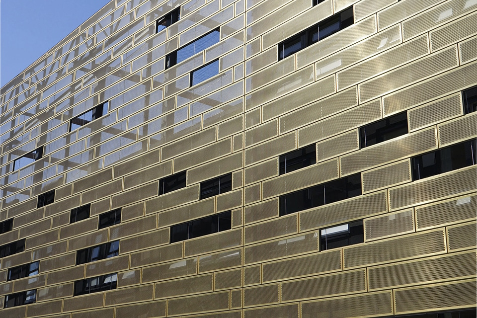Wall and a window of the Deptford Lounge located in London, UK. Walls are clad from Nordic Royal Copper by Aurubis and Nordic Copper. Copper walls are gold-coloured and sunlight is reflecting from them.