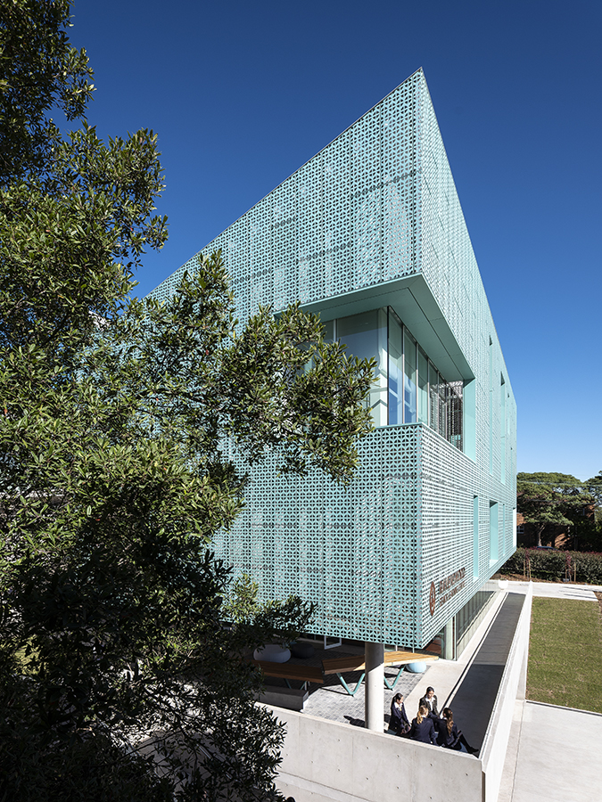 Close-up of the corner of the Ravenswood school in Sydney, Australia. The building's walls are clad from Nordic Blue copper.