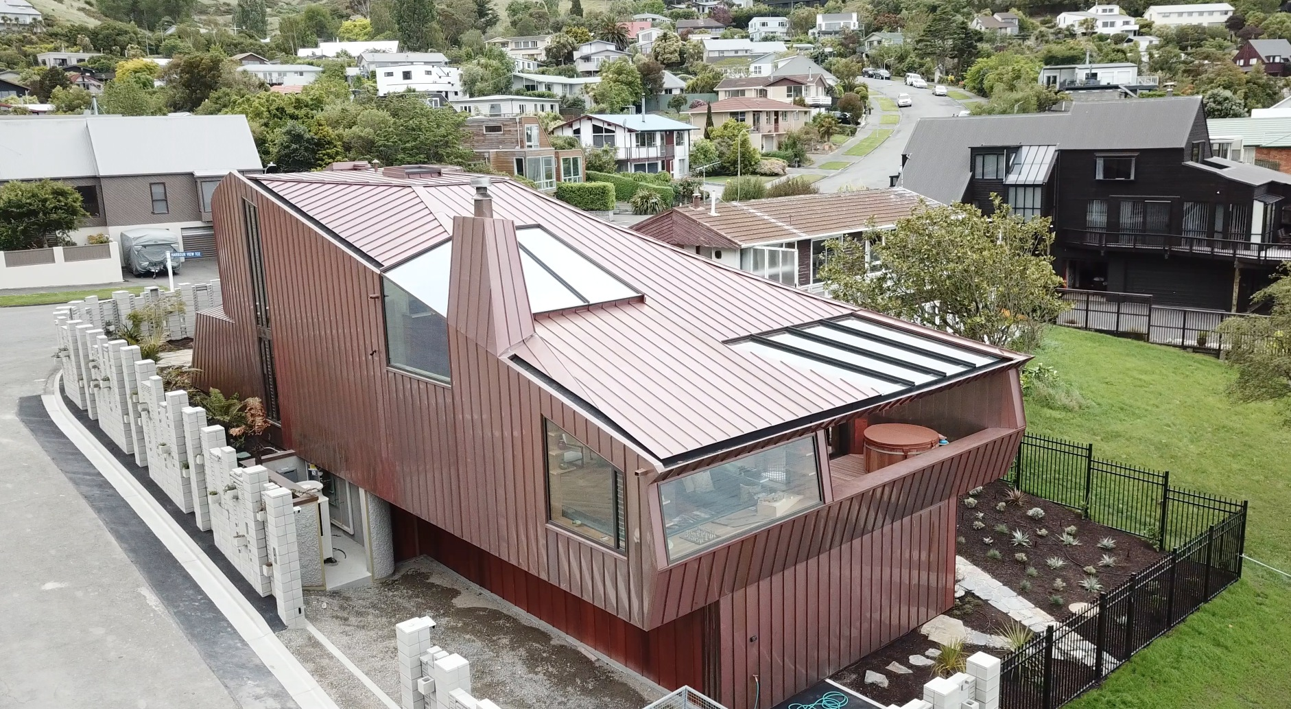 Drone shot of the Cass Bay House in New Zealand. The aerial view showcases the house and its surroundings. The copper elements of the house are clad from Nordic Standard copper.