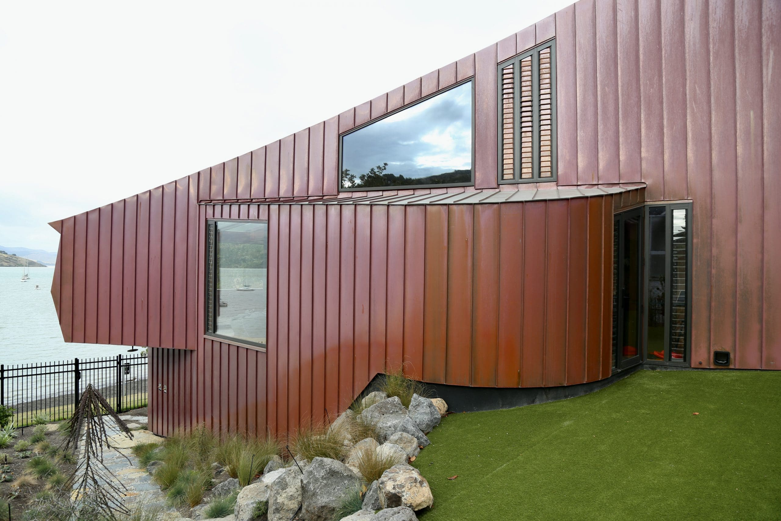 Side view of the Cass Bay House located in New Zealand. The copper walls are clad from Nordic Standard copper and have two windows in them.