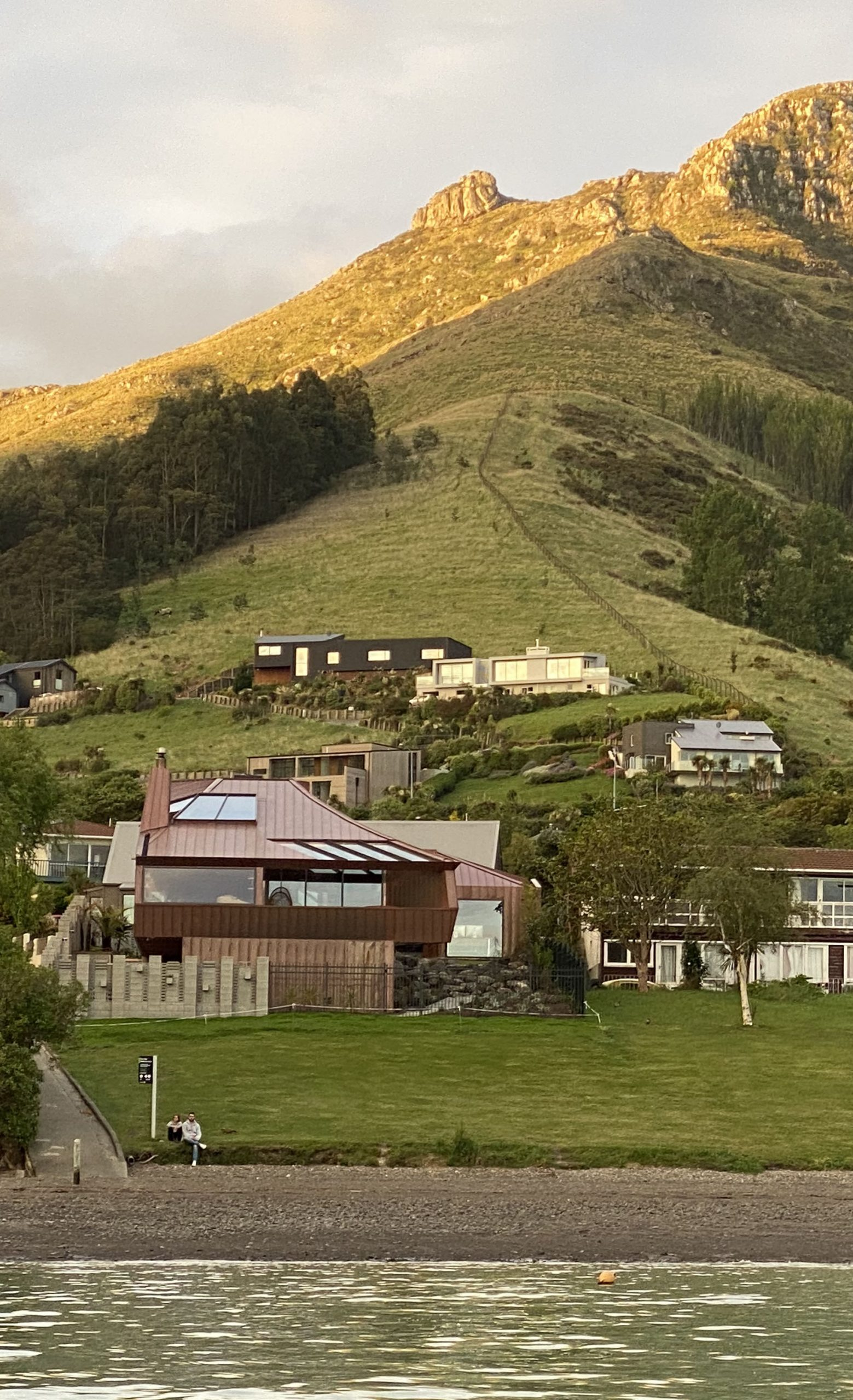 Hillside view of the Cass Bay House in New Zealand. The building's copper walls are clad from Nordic Standard copper.
