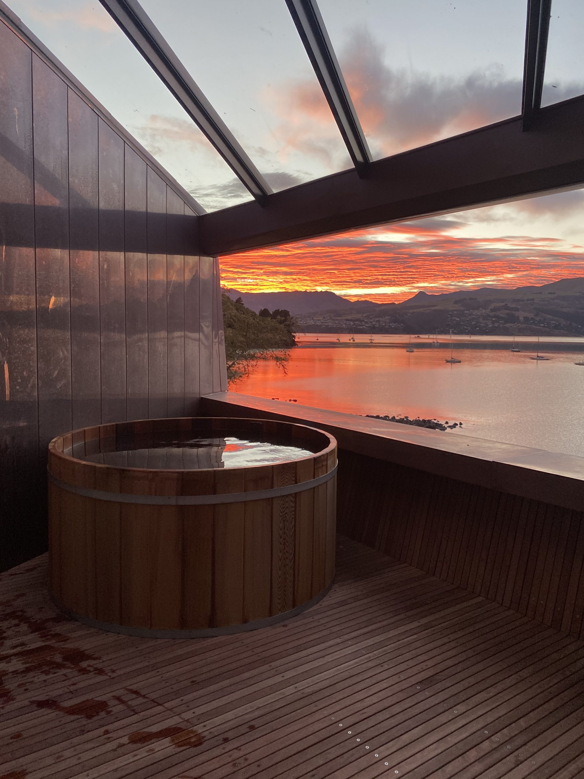 Sunset view of the balcony on the Cass Bay House in New Zealand. The wall and roof panels are clad from Nordic Standard copper.