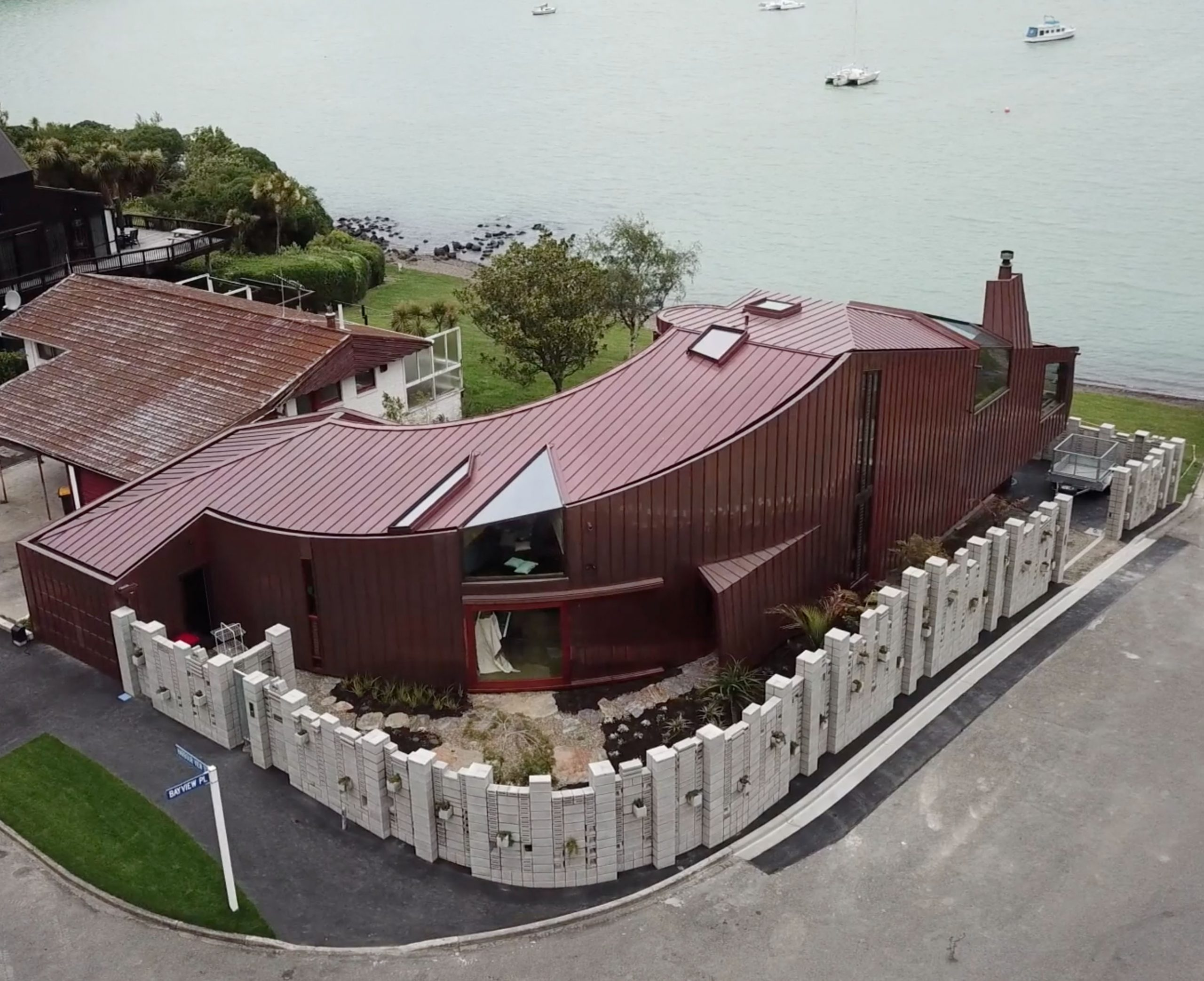 Aerial view of the Cass Bay House located in New Zealand. Some water is visible in the background. The copper walls of the building are clad from Nordic Standard copper.